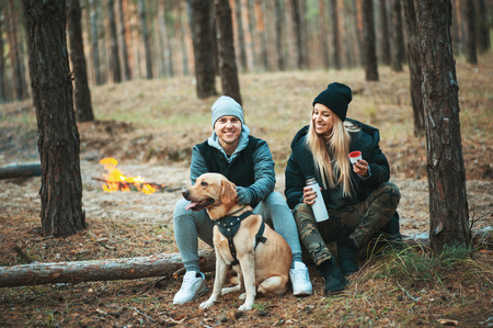 atmospheric: Romantic couple with dog sitting near bonfire, autumn forest background. Young blonde woman and handsome man. Concept - family, togetherness, love, friendship, travel.