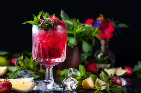 Glass of alcohol cold red coctail decorated with ice, fruit, flowers and mint staying on table in bar. Fresh juice on black background with lemon, strawberry lime.