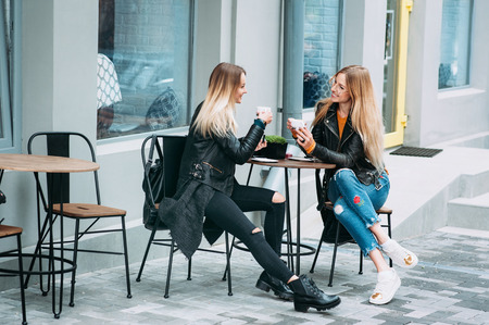 Two beautiful young women drinking coffee and gossiping in a nice restaurant outdoor. The weather is great and sunny for walking