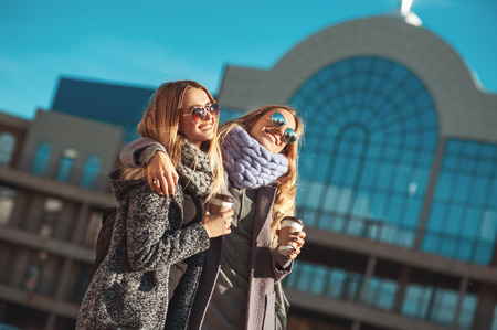 Two beautiful young women talking while walking the street after shopping holding the coffee and smiling. The weather is great today for walking with friend.