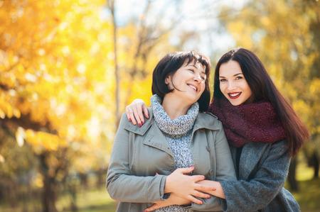 El retrato de la madre mayor y la hija hermosa adulta en parque del otoño están abrazando y están sonriendo, tiempo de la familia al aire libre. Generación de mujeres. Moda, personas, valores familiares, conceptos de vacaciones.