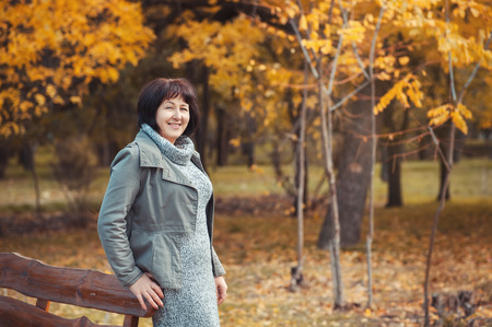 Mature senior woman is walking in autumn park dreaming, smiling and planning her day. She is happy, because she has a perfect health, nice family and great hobby. Life is bright and colorful. Stock Photo