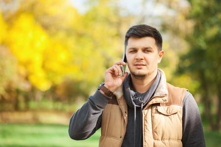 Hombre joven en el Parque de otoño hablando por teléfono inteligente con una seria emoción en la cara. Apuesto hombre de negocios hablando con alguien por teléfono. Personas, negocios, tecnología, comunicación, conceptos estacionales.