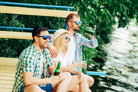Group of young people sitting on the dock near the lake, toasting with bottles, drinking beer and smiling. Men and woman chatting, relaxing, enjoying sunset. Friendship, having fun oktoberfest concept