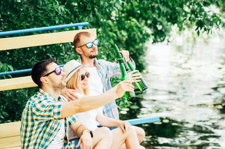 Grupo de jóvenes sentados en la playa brindando y bebiendo cerveza de botellas. Amistad, barbacoa, oktoberfest, conceptos relajantes. Buen tiempo con amigos al aire libre. Hombres y mujeres pasando el rato.