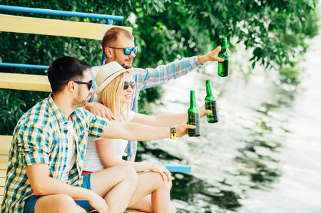 near beer: Group of young people sitting on the dock near the lake, toasting with bottles, drinking beer and smiling. Men and woman chatting, relaxing, enjoying sunset. Friendship, having fun oktoberfest concept
