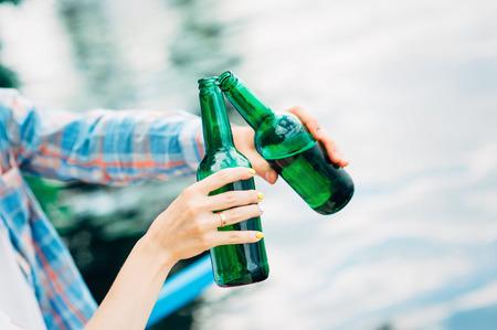 ¡Dia maravilloso! ¡Aclamaciones! Grupo de gente joven que se sostiene y que tuesta con las botellas verdes de cerveza en fondo del río. Celebrando el oktoberfest con amigos al aire libre. Barbacoa colgando, relajando conceptos. Foto de archivo