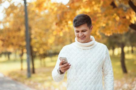 Hombre guapo joven en el parque de otoño y con smartphone. Empresario escribiendo mensaje a alguien. Personas, tecnología, comunicación, estudiante, conceptos de vida.