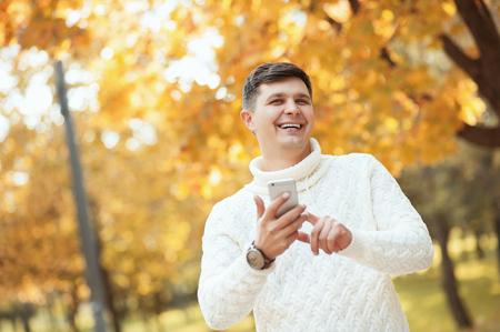 Es hora de tener un descanso! Hombre guapo joven de moda en suéter permanecer en el parque de otoño con smartphone y sonriendo. Fondo de otoño naranja. Negocios, estudiantes, comunicación, conceptos de personas.