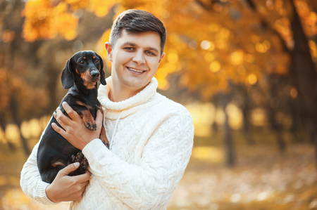 Happy free time with beloved dog! Handsome young man in autumn park smiling and holding cute puppy dachshund. Happy pets, friendship, emotions and love concepts.