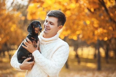¡Feliz tiempo libre con el perro amado! Hombre joven hermoso que se sienta en el parque soleado del otoño que sonríe y que sostiene el perro basset lindo del perrito. Felices mascotas, amistad, emociones y conceptos de amor. Foto de archivo