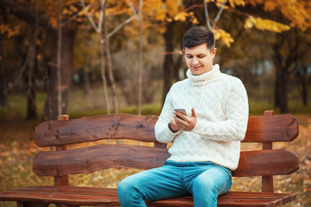 Call to me or write a message! Handsome young man in sweater and jeans using smartphone while sitting on the bench in the autumn park. Communication, technology, outdoor concepts.