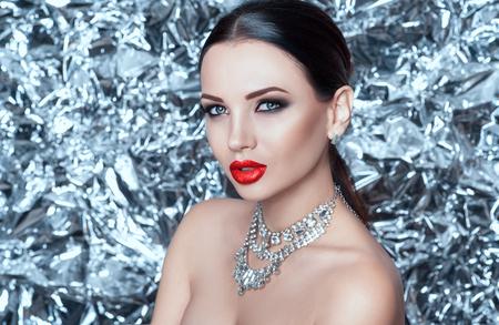 Retrato de una dama joven de glamour de lujo sobre un fondo plateado en una noche de año nuevo. Aspecto de año nuevo de modelo.