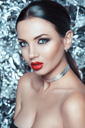 Retrato de bella joven con maquillaje de lujo y elegante accesorio en el cuello. Maquillaje de vacaciones en plata brillante fondo brillante.