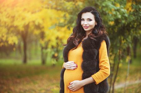 Hermosa joven feliz mujer embarazada. Esperando al bebé. Moda, belleza, familia, conceptos de personas. ¡Los niños son nuestra vida! Foto de archivo