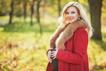 Beautiful pregnant woman standing in autumn park. Future Mom having pleasure time outdoors. Family, pregnancy, fall, people, season concepts. Stock Photo