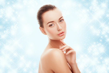 Beautiful young girl touching her face on a blue background and snow. Plastic surgery, facelift and rejuvenation concept. Fashion, holiday, cosmetology, people concept. Skincare on winter time. Stockfoto