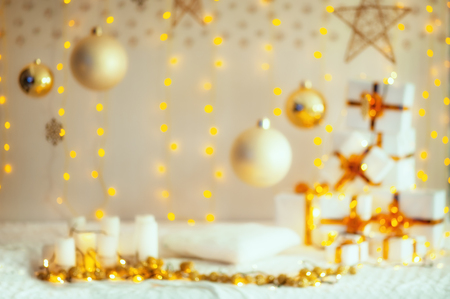 Christmas blurred decorating composition. Christmas gifts with gold ribbon, pillow, knitted blanket, christmas balls and stars at cozy home. New year celebration. Wallpaper, postcard, card.