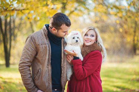 Buen momento para caminar! Hermosa pareja de familia con blanco lindo perro maltés pasar tiempo en el parque de otoño. El hombre y la mujer se divierten con su terrier mascota. Familia, animal, vida, gente, conceptos estacionales. Foto de archivo