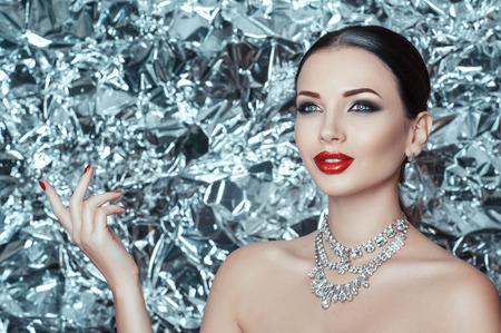 Muy hermosa joven con maquillaje de vacaciones y accesorios de diamantes está esperando un milagro en año nuevo. Reina de invierno. Fondo de plata hielo.