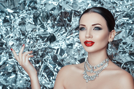 Very beautiful young lady with holiday makeup and diamond accessory is waiting for a miracle on new year. Winter queen. Ice silver background.