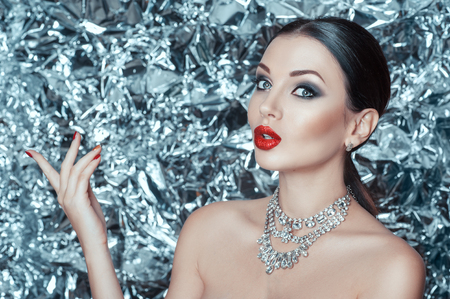 Red lips and shiny diamond jewelery on a glitter background. Surprised girl on new year night.