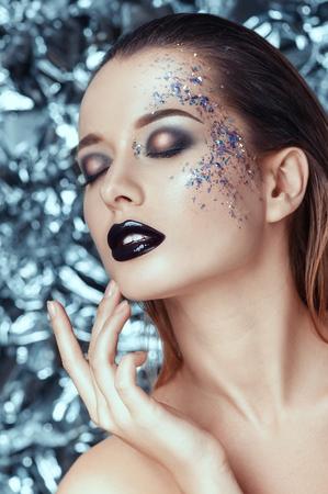 Sensual joven y bella mujer con maquillaje de noche brillantes sobre fondo de Navidad. personas, belleza, moda, cosméticos, vacaciones y concepto de la magia.