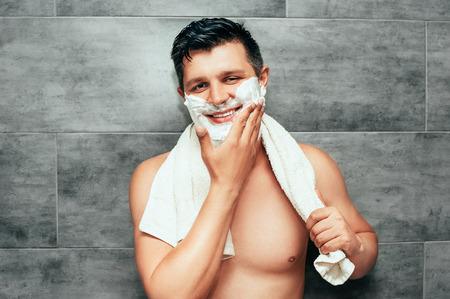 Joven guapo sentado en el baño con una toalla sobre los hombros sonriendo y aplicar espuma de afeitar. Chico con cuerpo sexy listo para afeitarse.