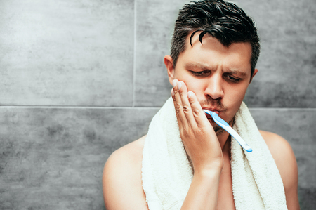 Toothache. Frustrated young handsome man touching his cheek while brushing teeth in bathroom. sensitive teeth and gums. Dental hygiene, health care, beauty and people concept. Stock Photo