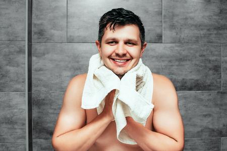 Apuesto joven de pie en el baño con una toalla blanca en los hombros. Morena musculoso con un torso sin camisa sosteniendo una toalla y el cuidado de la piel de su rostro, comprobando su concepto de bienestar de la piel de la barba.