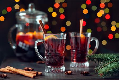 El invierno tradicional reflexionó sobre el vino en el ornamento del vidrio y de la Navidad del vintage en fondo de las luces, el foco selectivo y la imagen entonada. Sangría en la mesa de vacaciones. Celebración de acción de gracias con cóctel picante.