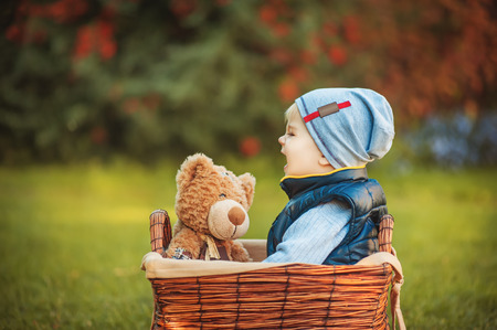 Happy little boy playing with a toy. Children enjoying activity outdoor. Childhood, baby, holiday, people, hobby, emotions concepts. Stock Photo