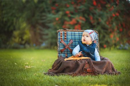 Niño pequeño feliz que juega con el juguete del aeroplano mientras que se sienta en maleta en césped verde del otoño. Niños disfrutando de la actividad al aire libre. Conceptos de infancia, bebé, vacaciones, gente, afición. Foto de archivo