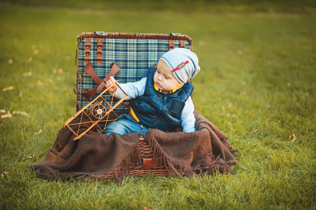 Happy little boy playing with airplane toy while sitting in suitcase on green autumn lawn. Children enjoying activity outdoor. Childhood, baby, holiday, people, hobby concepts.