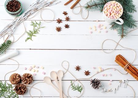 Composición de marco de cacao con malvavisco, canela, estrellas de anís, semillas de café, abeto, palos, cucharas e ingredientes con cosas con espacio de copia en la mesa blanca. Invierno, otoño, cocina, endecha plana