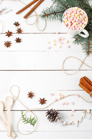 Card Frame composition of Cocoa, Marshmallow, Cinnamon, Anise Stars, Coffee Seeds, Fir Tree, Spoons Ingredients Stuff with copy space on white table. Autumn Kitchen Winter concepts. Flat Lay