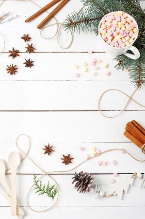 Composición de marco de tarjeta de cacao, malvavisco, canela, estrellas de anís, semillas de café, abeto, cucharas Ingredientes Rellene con espacio de copia en la mesa blanca. Conceptos de Autumn Kitchen Winter. Lay Flat