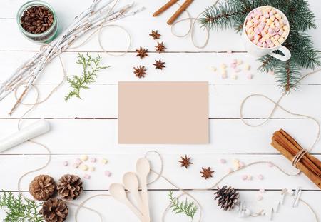 Enmarque la composición de cacao con malvavisco, canela, estrellas de anís, semillas de café, abeto, cucharas e ingredientes con tarjeta transparente en el centro sobre fondo blanco. Copie el espacio, el otoño, los conceptos de cocina.