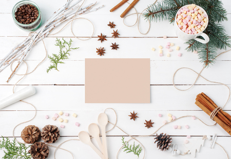 Frame composition of cocoa with marshmallow, cinnamon, anise stars, coffee seeds, fir tree, spoons and ingredients with clear card on center on white background. Copy space, autumn, kitchen concepts.