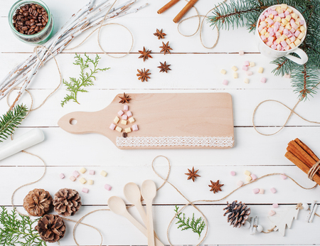 Frame christmas composition of cocoa with marshmallow, cinnamon, anise stars, coffee seeds, fir tree, spoons and ingredients with chopping board on center decorated with made new year tree and lace.