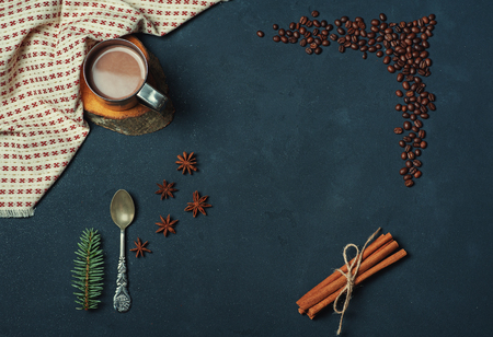 Frame of the Cup of Cacao Coffee Beans Cinnamon sticks Spoon and Fir Branch on Dark Texture Table decorated with Napkin. Kitchen Ingredients Winter or Autumn Composition. Flat lay Top view Copy Space