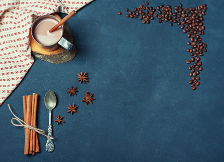 Frame of the Cup of Cacao Coffee Beans Cinnamon sticks Spoon on Dark Texture Table decorated with Napkin. Kitchen Ingredients Winter or Autumn Composition. Flat lay Top view Copy Space