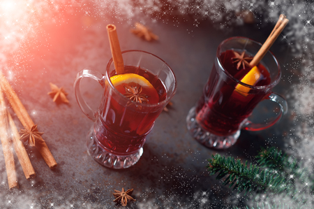 Traditional winter mulled wine in vintage glass and christmas tree on old background decorated cinnamon anise stars and snow frame Holiday Drink Celebrating Alcohol Autumn Cocktail Texture Concept