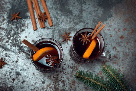Traditional winter mulled wine in vintage glass and christmas tree on old background decorated cinnamon and anise stars. Holiday Drink Celebrating Alcohol Autumn Cocktail Texture Concept Flat lay