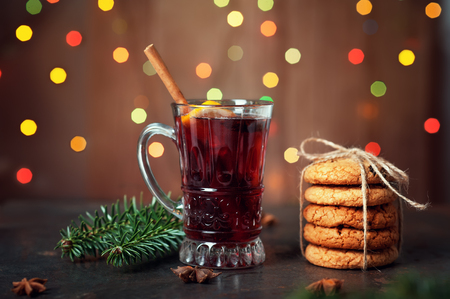 Cup with red mulled wine or sangria and gingerbread cookies for Christmas table on holiday background with bokeh lights. Winter New Year Thanksgiving atmosphere Magic evening Food Concept