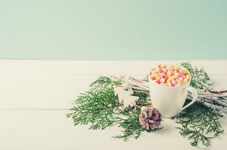 Composición de invierno de taza de cacao con Marshmallow decorado ramas de abeto y cono de pino sobre fondo blanco de madera Enfoque selectivo Tono de color de la vendimia. Año nuevo o tarjeta de Navidad con copia espacio