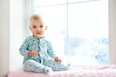 Cute adorable little baby girl sitting by window and looking to cam. Kid enjoy snowfall. Happy holidays and Christmas! Winter Home Family. copy space.