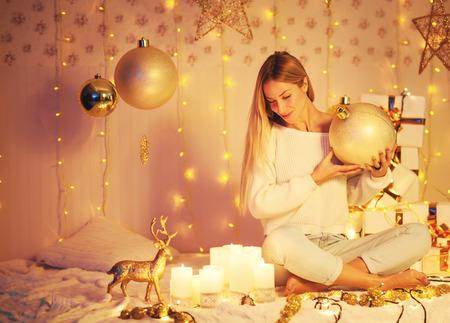 Hermosa mujer joven sentada en un árbol de Navidad de fondo. ¡Feliz navidad y próspero año nuevo! belleza de invierno Foto de archivo