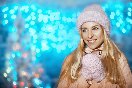 Merry Christmas and Happy New Year! Portrait of happy cheerful beautiful woman in knitted hat and mittens holding outdoor on christmas blue background and smiling. Cold Winter Warm Emotion Concept