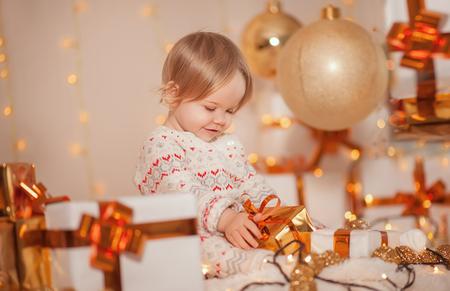 Feliz Navidad y Felices Fiestas! Pequeña niña linda del cabrito que se sienta en una habitación moderna que sostiene un actual rectángulo con sorpresa y la sonrisa. Conceptos de familia de bebé año nuevo.
